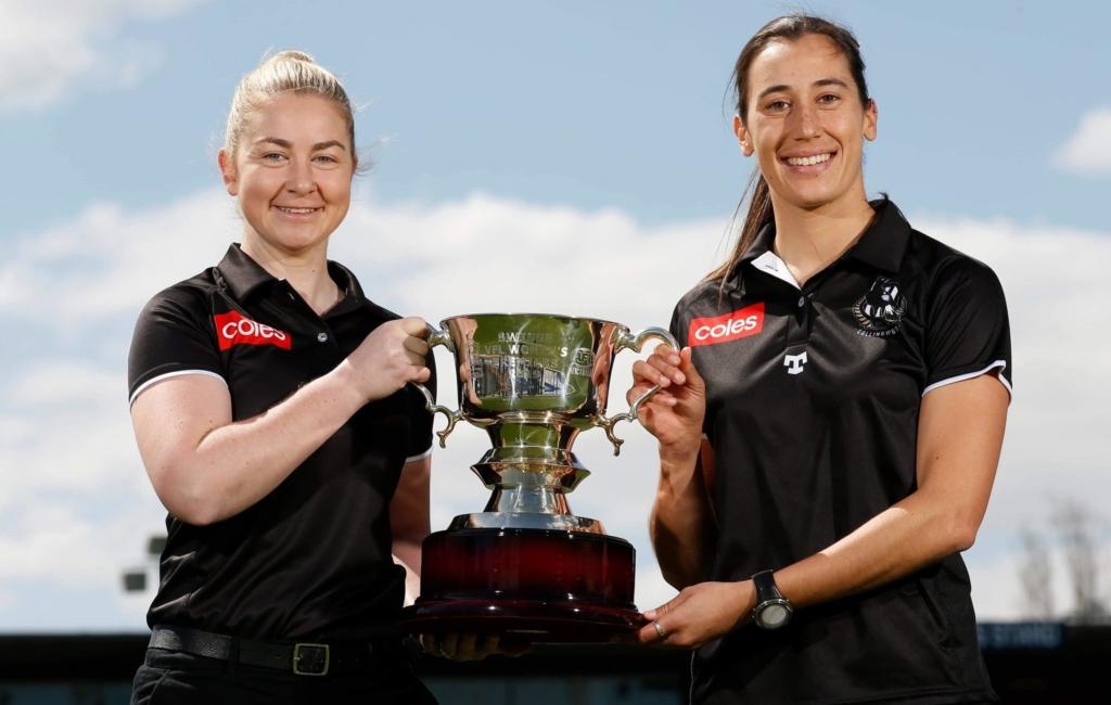 Alumni Grace Buchan and Penny Cula-Reid hold VFL premiership cup